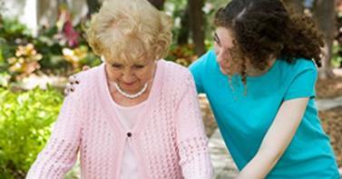 Caregiver Helps Elderly Woman on Walker